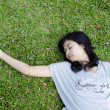图库照片: Young model laying in grass