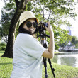 Beautiful smiling asian girl with camera — Stock Photo