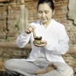 Woman playing a tibetan bowl, traditionally used to aid meditati — Stock Photo