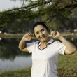 Happy asian woman posing against a background of trees — Стоковая фотография