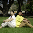 Portrait of beautiful couple sitting on ground in park — Stock Photo