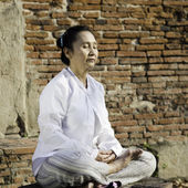 Woman meditating against ancient temple — Stock Photo