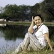 Woman sitting on green field by lake — Stock Photo
