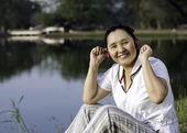 красивая женщина азии прослушивания музыки в наушниках — Стоковое фото