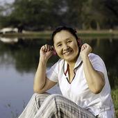 Beautiful asian woman listening music in headphones — Stock Photo