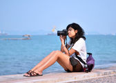 Young female photographer taking pictures on beach — Stock Photo
