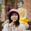 Beautiful young girl and buddha at Wat Yai Chai Mongkol Temple — Stock Photo #23909461