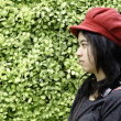 Asian girl with red hat on a background of green nature — Stock Photo