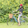 Smiling girl riding a bicycle in the park — Stock Photo