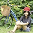 Girl with a bicycle rests on a grass — Stock Photo