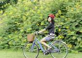 Happy smiling girl riding a bicycle in the park — Stock Photo