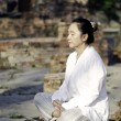 Asian woman meditating in ancient buddhist temple — Stock Photo #25841231