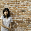 Young Asian woman against a Brick Wall  — Stock Photo