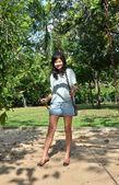 Mulher está de pé em um balanço em um cenário de parque — Fotografia Stock
