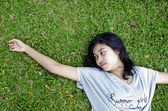 Young asian woman laying in the grass — Stock Photo