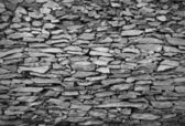 Cracked real stone wall surface with cement in black and white t — Stock Photo