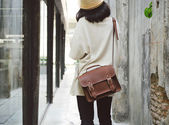 Fashion girl with leather bag at concrete alleyway — Stock Photo