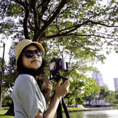 Girl with camera in public park — Stock Photo