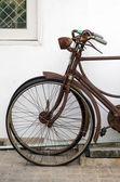 Oude roestige fiets in de buurt van betonnen wand — Stockfoto