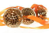 Three golden balls with orange ribbon — Stock Photo