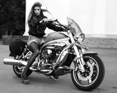 Shot of young woman on a motorbike looking sexy — Stock Photo