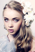 Closeup fashion color portrait of young model with flowers and j — Stock Photo