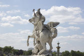 Ancient sculpture in Paris over the blue sky — Stock Photo