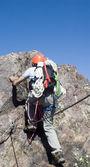 Climber climbing a vertical wall of a mountain — Stock Photo