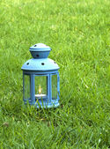 Blue Lantern, with burning candle inside, on green grass  — 图库照片