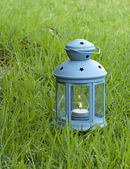 Blue Lantern, with burning candle inside, on green grass  — Stock Photo