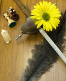 Ancient sword, a candle, a yellow flower, two pieces of chess an — Stock Photo