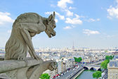 Gargoyle in Notre Dame Cathedral, Eiffel Tower on background. — Stock Photo