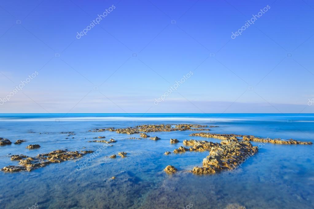 Rocks in a blue ocean under clear sky on sunrise. � Foto stock ...