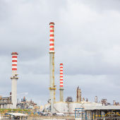 Oil refinery industry, smoke stacks on cloudy sky background — Stock Photo