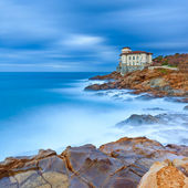 Boccale castle landmark on cliff rock and sea. Tuscany, Italy. Long exposure photography. — Stock Photo