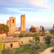 San Gimignano landmark medieval town on sunset, towers and park. — Stock Photo