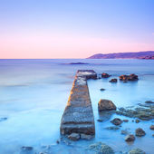 Concrete pier or jetty and rocks on a blue sea. Hills on backgro — Stock Photo