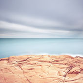 Cliff rocks, blue ocean and cloudy sky background. — 图库照片