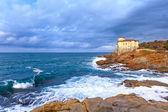 Ocean wave y boccale castillo hito en la roca del acantilado. toscana, italia. — Foto de Stock