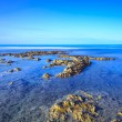 Rocks in a blue ocean under clear sky on sunrise. — Stock Photo