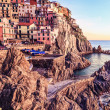 Manarola village, rocks and sea at sunset. Cinque Terre, Italy - Stock Photo