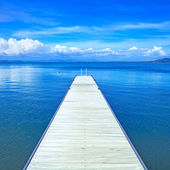 Wooden pier or jetty on a blue ocean. Beach in Argentario, Tuscany, Italy — Stock Photo