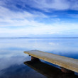 Concrete pier or jetty and on a blue lake and sky reflection on water. — Stock Photo