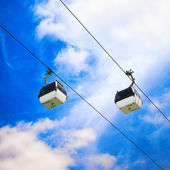 Two cable car on a partly cloudy sky background — Stock Photo