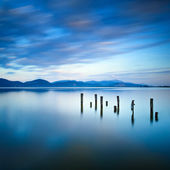 Wooden pier or jetty remains on a blue lake sunset and sky reflection on water. Versilia Tuscany, Italy — Stock Photo