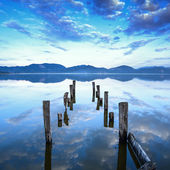Wooden pier or jetty remains on a blue lake sunset and sky reflection on water. Versilia Tuscany, Italy — Zdjęcie stockowe