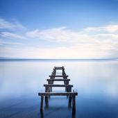 Muelle de madera o restos del embarcadero en el lago azul. larga exposición. — Foto de Stock