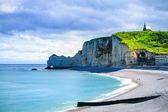 Etretat cliff, church landmark and beach on morning. Normandy, F — Stock Photo