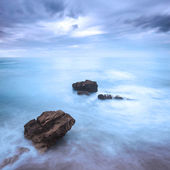 Rocks in a ocean waves under cloudy sky. Bad weather. — Stock Photo