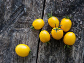 Yellow tomatoes on wooden background — Stock fotografie
